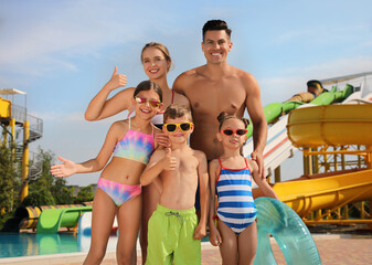 Fototapeta Happy family with inflatable ring near pool in water park obraz