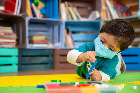 Mexican baby in school with face mask playing with colored pieces on a mat, back to school