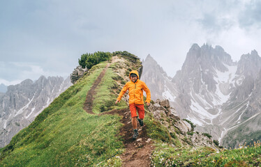 Fototapeta Dressed bright orange soft shell jacket backpacker running  by green mountain path with picturesque Dolomite Alps range background,. Active people and European mountain hiking tourism concept image. obraz