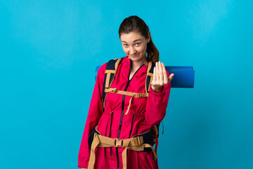 Fototapeta Young mountaineer woman over isolated blue background inviting to come with hand. Happy that you came obraz