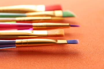 Fototapeta Set of different paintbrushes on orange background, closeup obraz