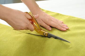 Fototapeta Seamstress cutting light green fabric with scissors at workplace, closeup obraz