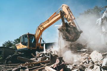 Fototapeta Destruction of old house by excavator. Bucket of excavator breaks concrete structure. obraz