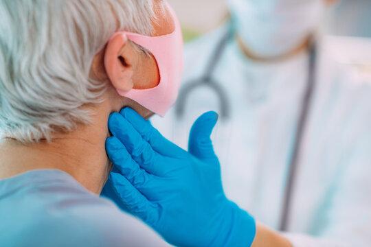 Doctor Examining Senior Woman with Thyroid Gland Problem.