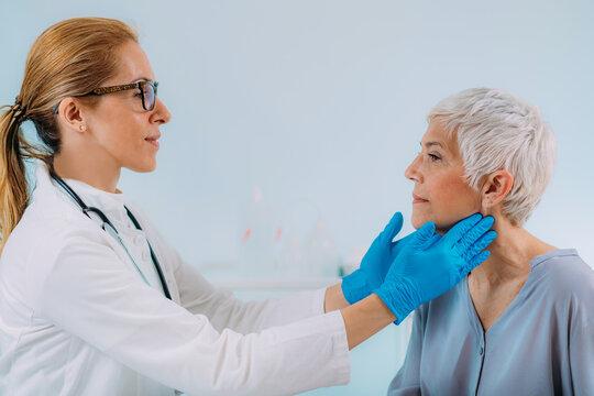Doctor Examining a Senior Woman with Thyroid Gland Disease Symptoms