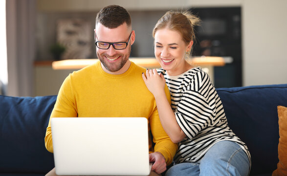 Young happy family couple using laptop while sitting on sofa at home