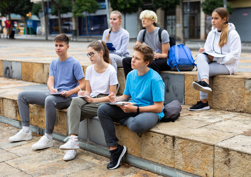 Group of teen students sitting with workbooks in schoolyard in warm autumn day.