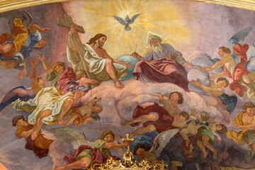 VIENNA, AUSTIRA - JULI 5, 2021: The fresco of Holy Trinity in Jesuitenkirche - Jesuits church by jesuit Andrea Pozzo from begin of 18. cent.