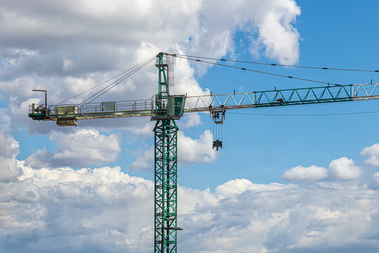 Green construction crane on a sky background