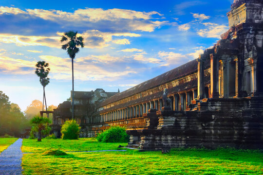 Angkor Wat. Beautiful scenic view of back wall at sunrise with erly morning mist, cloudy blue sky and fresh green grass in front of temple, sun rise, Siem Reap, Cambodia, South East Asia