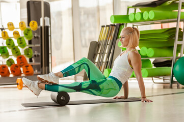 Fit woman relaxes muscles after intense workout with massage roller