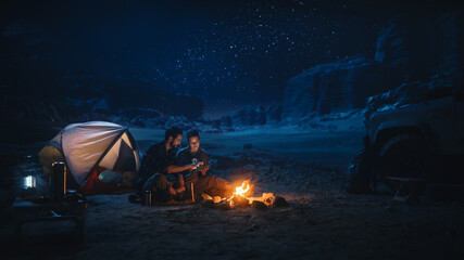 Fototapeta Happy Couple Camping in the Canyon at Night, Use Digital Tablet Computer, Sitting by Campfire. Two Traveling people Have Fun, Smile, Post on Social Media, Watch Funny Videos on Internet obraz