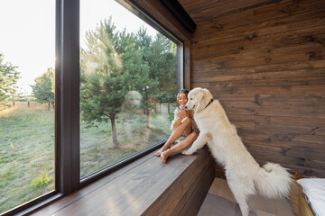 Obraz Young woman resting at beautiful country house or hotel, sitting on the window sill with pine forest view and hugs with big white dog. Concept of solitude and recreation on nature with pet - fototapety do salonu