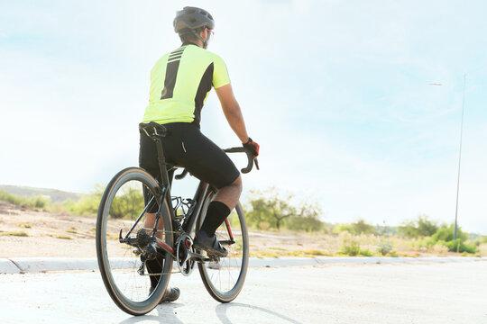 Latin athlete cycling and looking at the horizon