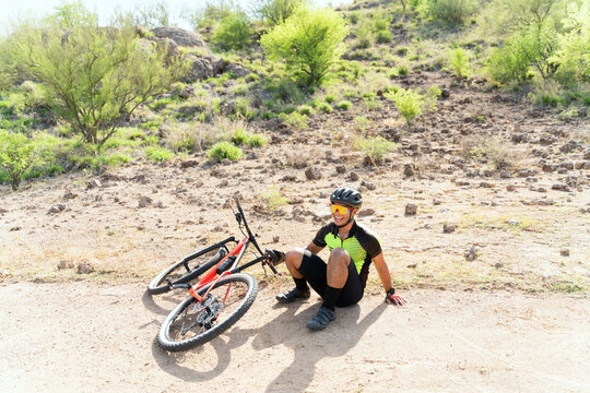 Handsome athlete sitting on a trail next to his bike