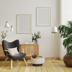 Two poster mockup with vertical frames on empty white wall in living room interior and armchair.