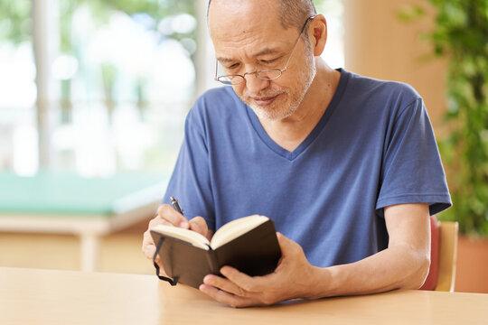 スケジュール帳に記入する高齢者