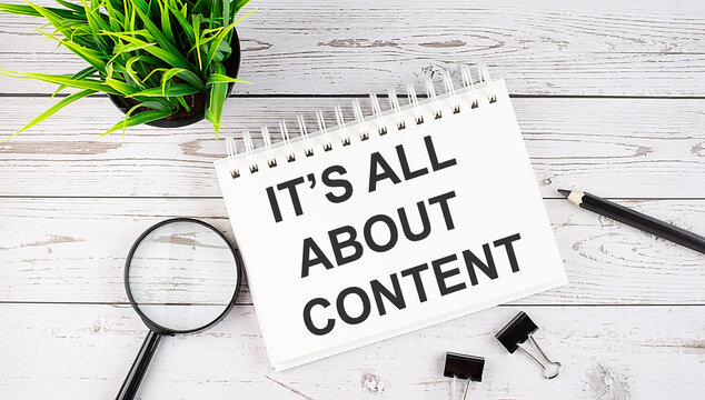 IT'S ALL ABOUT CONTENT text concept write on notebook with office tools on the wooden background