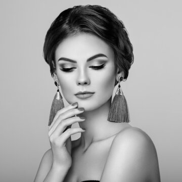 Beautiful Woman with Large Earrings Tassels jewelry. Perfect Makeup and Elegant Hairstyle. Nails manicure