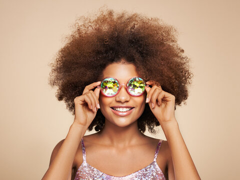 Beauty portrait of African American girl in colored holographic sunglasses. Beautiful black woman on pink background. Cosmetics, makeup and fashion