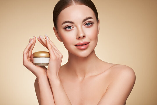 Beauty woman applying cream on her face. Young woman with clean fresh skin. Model with a jar of face cream