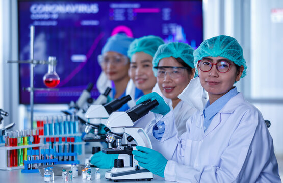 Group of female researchers or scientists wearing protective hygiene masks and medical uniforms sitting together and working with microscopes and test tube in laboratory and looking to camera