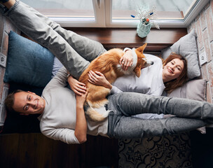 Top view of beautiful couple looking at camera and smiling while lying on widow seat with adorable...