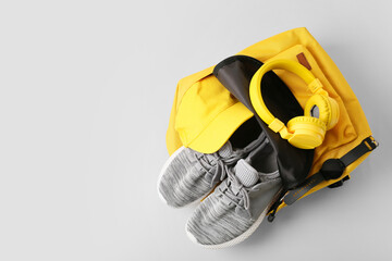 Backpack with sport shoes, headphones and smart watch on grey background