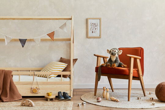 Stylish composition of cozy scandinavian child's room interior with wooden bed, red armchair, plush and wooden toys and hanging decorations. Neutral wall, carpet on the floor. Copy space. Template.