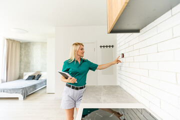 Fototapeta woman regulating heating temperature with a modern wireless thermostat installed on the white wall at home. Smart home heating regulation concept obraz