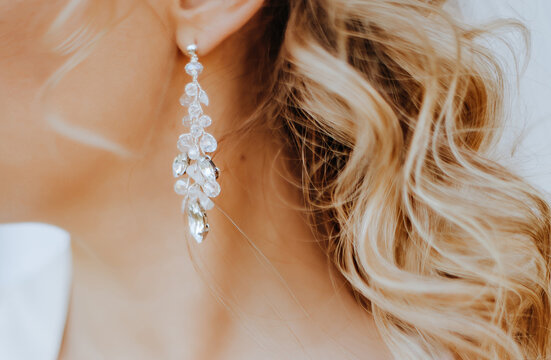 The bride puts on beautiful wedding earrings. Girl with hairstyle with curls wears jewelry accessories