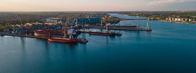 Fototapeta Industrial port in the field of import-export global business logistics and transportation, Loading and unloading container ships, cargo transportation from a bird's eye view. obraz