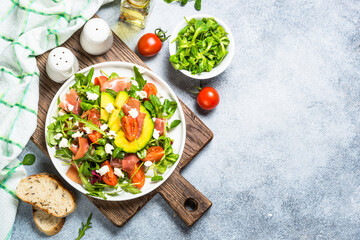 Green salad with avocado, salad leaves, jamon and tomatoes. Healthy diet food. Top view at light stone table.