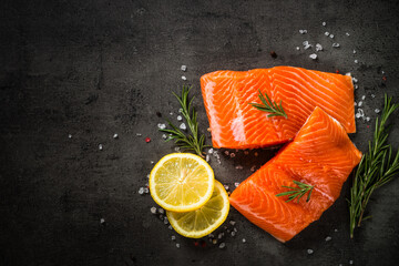 Salmon fillet at cutting board with ingredients for cooking at black. Fresh fish. Top view with copy space.