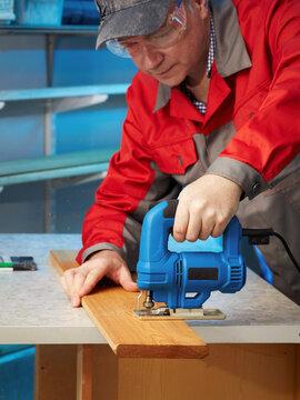 A carpenter  cuts planks