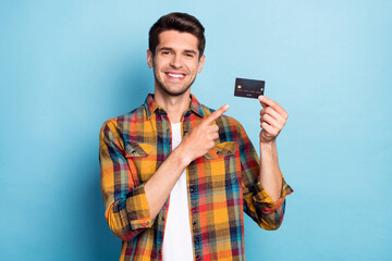 Portrait of attractive cheerful guy holding in hand demonstrating bank card deposit isolated over...