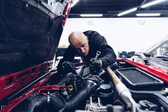 Man car service worker fixing or regulating engine with his tools