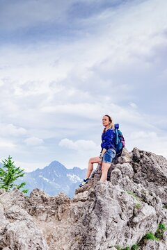 Woman traveler standing on a rock in the mountains. He admires the beautiful mountain views.