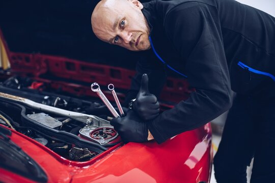 Mechanic working in car service holding tools and wrench and showing ok sign