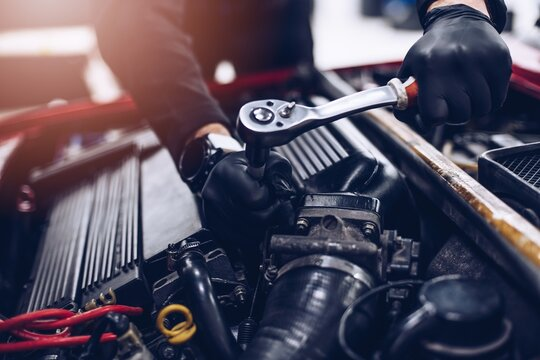 Car mechanic in service repairing engine with wrench