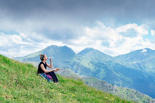 Woman traveler drinks water with a view of the mountain landscape. Trekking concept.