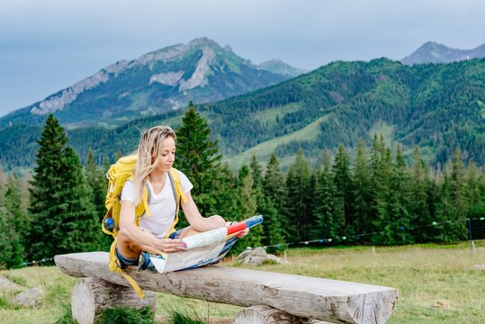 Girl traveler with yellow backpack sitting on a bench with a paper map.