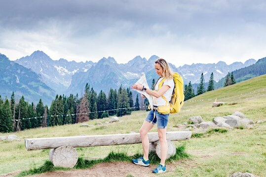 Happy female hiker with paper map in the mountains. Active recreation.