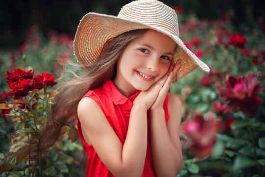 Beautiful little girl in roses garden in park. Charming woman smiling outdoor with flowers.