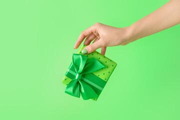 Fototapeta Female hand with gift box on color background obraz