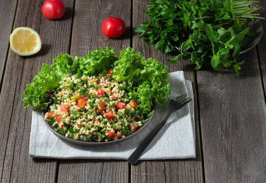 Tabbouleh salad, in a dark plate, cooked with boiled bulgur, herbs, lettuce, tomatoes, lemon, seasoned with olive oil on a wooden background.