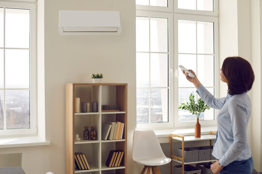 Woman switches wall air conditioner at home. Young lady standing in her modern light living room and setting comfortable temperature mode with remote control