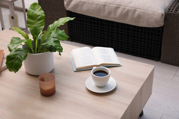 Coffee, candle, book and houseplant on wooden table indoors