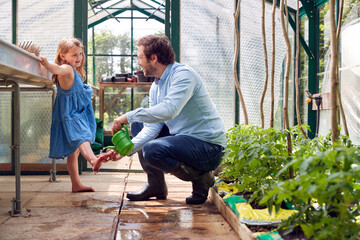 Father Washes Daughter's Feet Using Watering Can As She Helps Him In Greenhouse At Home
