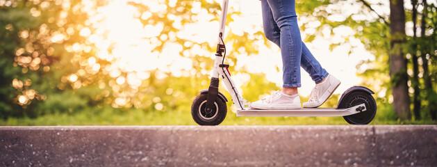 Fototapeta Woman riding on scooter in park in summer obraz